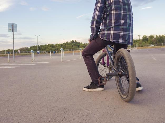 Casual adolescente sentado relaxando na bicicleta no grande campo de esportes de asfalto Foto Premium
