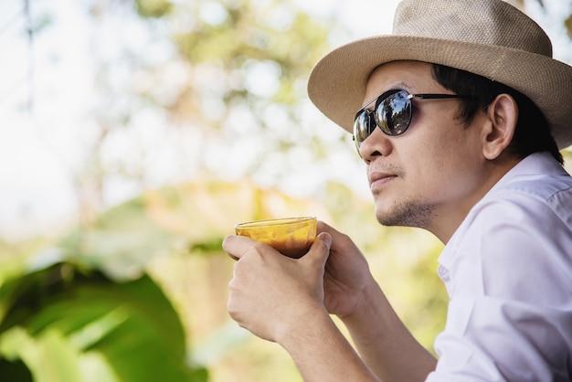 Casual, asiático, homem, bebida, café quente, felizmente, em, natureza Foto gratuita