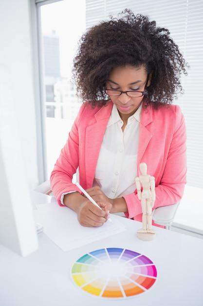 Casual designer gráfico trabalhando na mesa dela esboçar Foto Premium