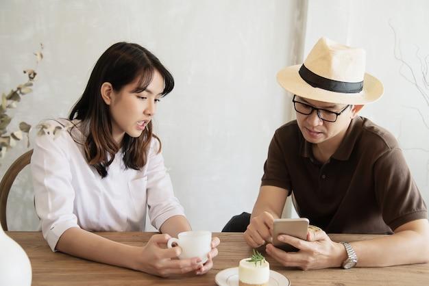 Casual, homem mulher, falando, felizmente, enquanto, bebida, café, e, olhar, telefone móvel Foto gratuita