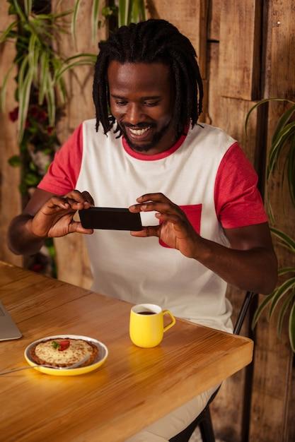 Casual homem tirando foto de pastelaria e café Foto Premium