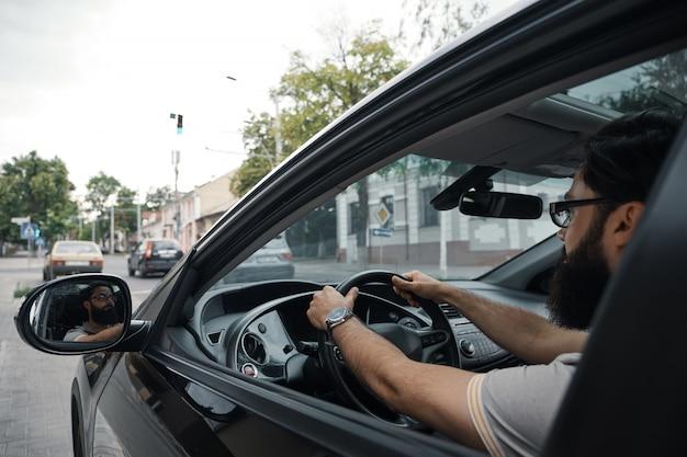 Casual moderno barbudo homem dirigindo um carro Foto gratuita