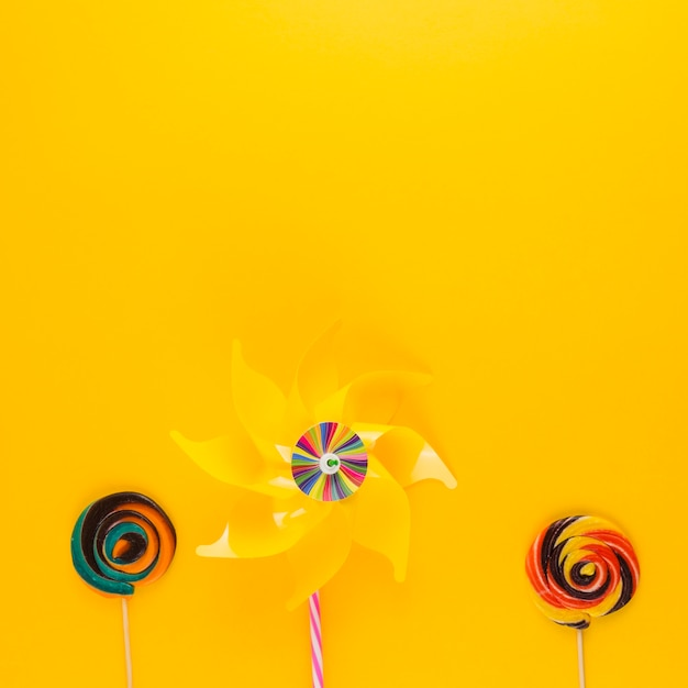 Cata-vento com pirulitos de redemoinho no pano de fundo amarelo Foto gratuita