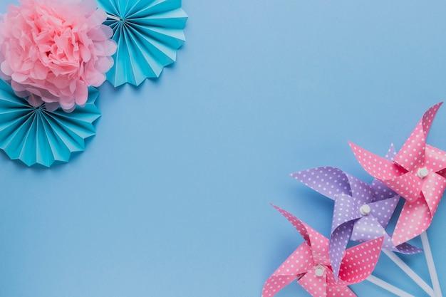 Cata-vento criativo e flor de papel bonito no canto do fundo liso Foto gratuita