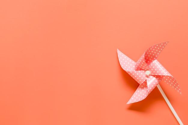 Cata-vento de brinquedo em fundo laranja Foto gratuita