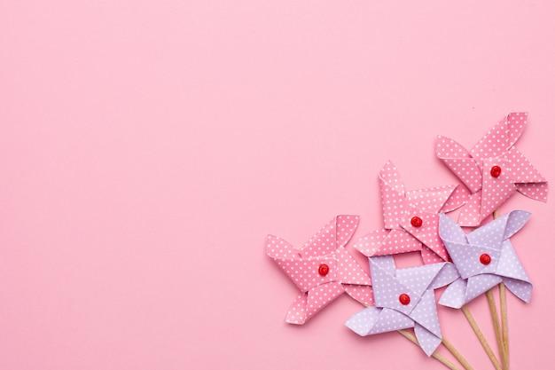 Cata-vento de moinho de vento de papel lilás e rosa em fundo rosa Foto Premium