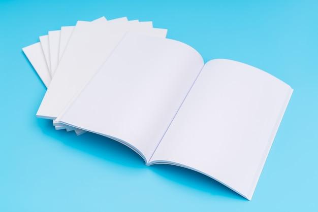 Catálogo em branco, revistas, livro mapeado no fundo azul. . Foto gratuita