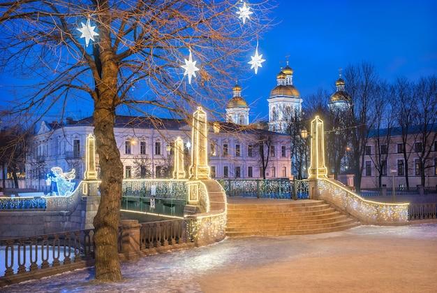 Catedral naval de nikolsky e estrelas festivas em uma árvore em são petersburgo e a ponte krasnogvardeisky sob o céu azul noturno Foto Premium
