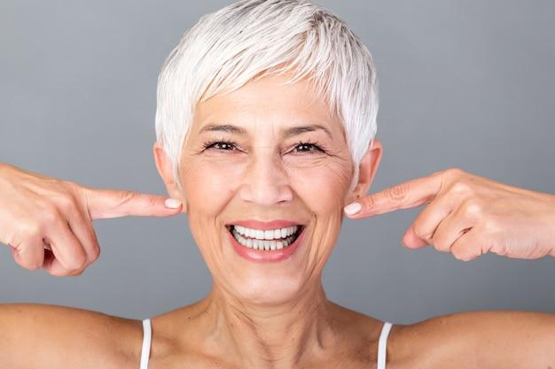 Caucasiana sorridente mulher sênior bonita cabelos grisalhos, apontando para os dentes e olhando para a câmera. fotografia de beleza. Foto Premium