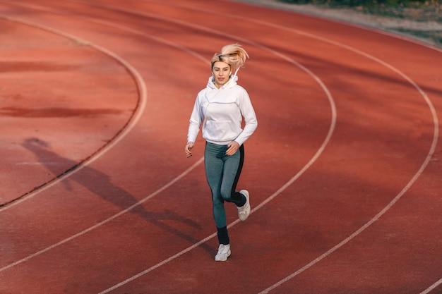 Caucasiano corredor feminino no sportswear correndo no estádio com fones de ouvido nos ouvidos. Foto Premium