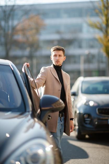 Caucasiano jovem atraente está abrindo uma porta de carro, vestido com casaco bege no centro da cidade em um dia ensolarado Foto gratuita
