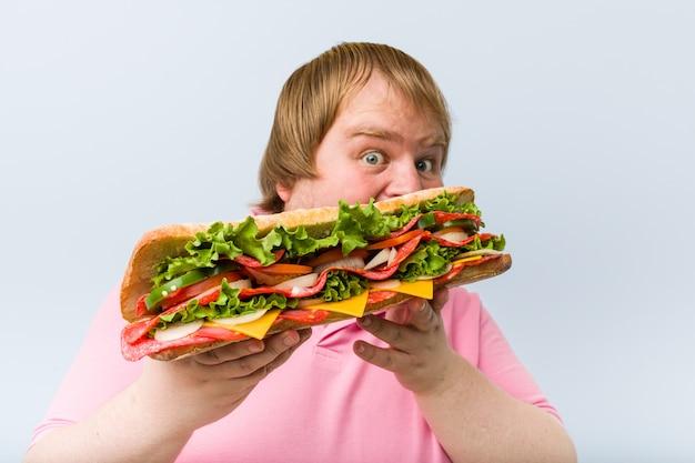 Caucasiano louco loiro gordo segurando um sanduíche gigante Foto Premium