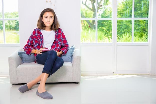 Caucasiano, menina adolescente, jogando smartphone, ou, tabuleta, pc, ligado, sofá, casa Foto Premium