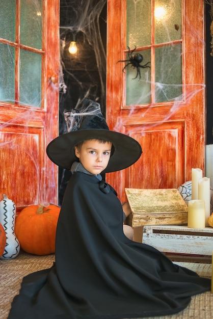 Caucasiano, menino, em, carnaval, assistente, traje, leitura, livro mágico, ligado, dia das bruxas, decoração, fundo Foto Premium