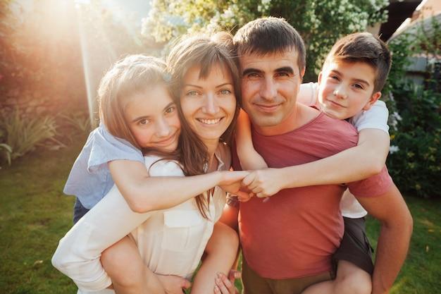 Caucasiano, pai, carregar, seu, crianças, parque Foto gratuita