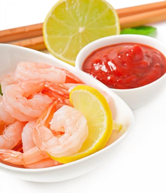 Caudas de camarão com limão fresco e alecrim em uma tigela branca Foto gratuita
