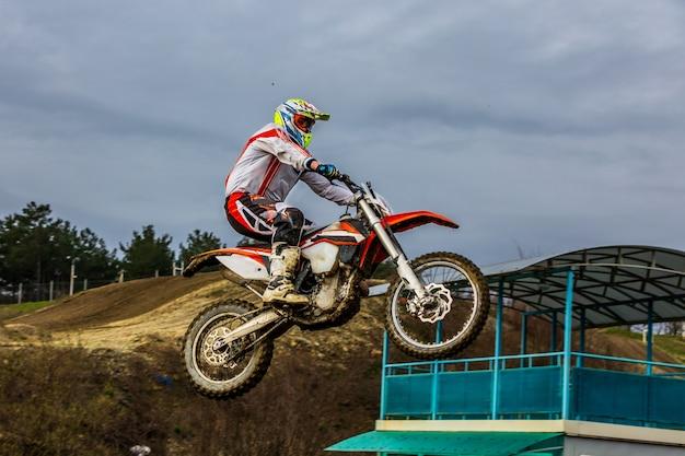 Cavaleiro da bicicleta da sujeira está voando alto Foto Premium