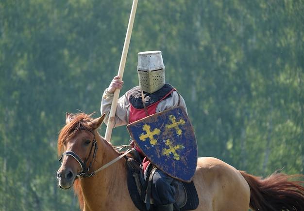 Cavaleiro medieval com uma lança, montando um cavalo em um fundo de floresta verde no campo. reconstrução histórica Foto Premium