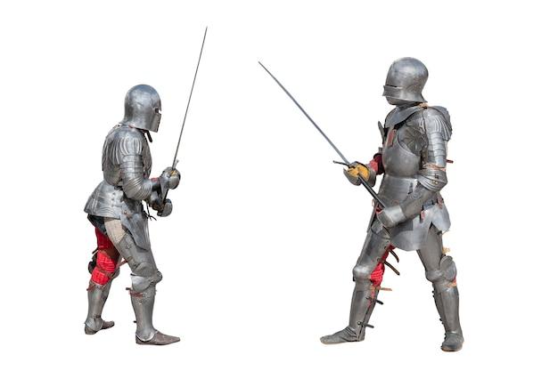 Cavaleiros de armadura. cavaleiros medievais em armaduras de ferro têm espadas nas mãos. duelo dos guerreiros medievais. batalha de dois cavaleiros em espadas. Foto Premium