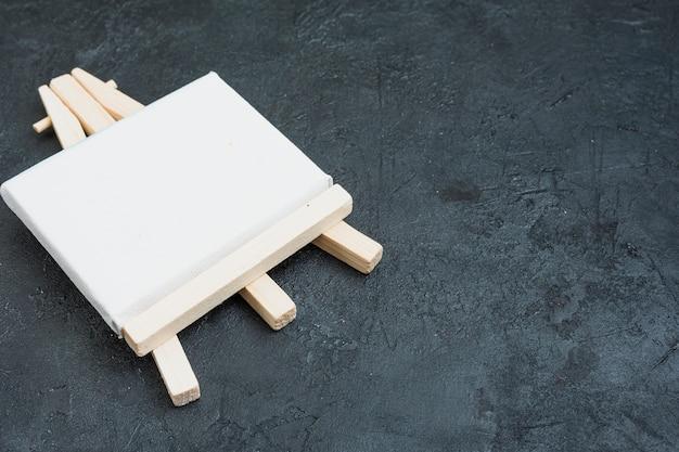 Cavalete de madeira em miniatura em branco sobre fundo de ardósia preta rock Foto gratuita