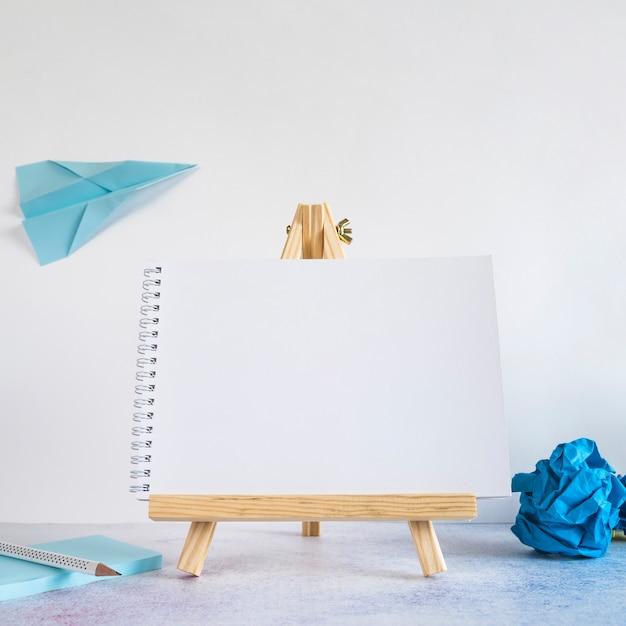 Cavalete pequeno com avião de papel na mesa Foto gratuita