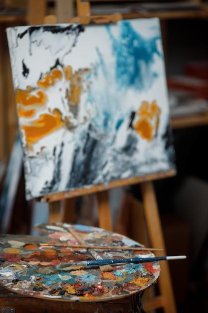 Cavalete, pincéis, tintas e paleta em uma oficina de arte Foto Premium