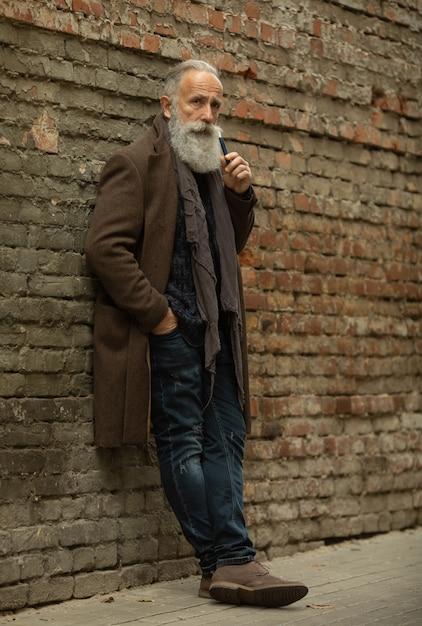 Cavalheiro elegante com barba longa fumar ao ar livre. Foto Premium