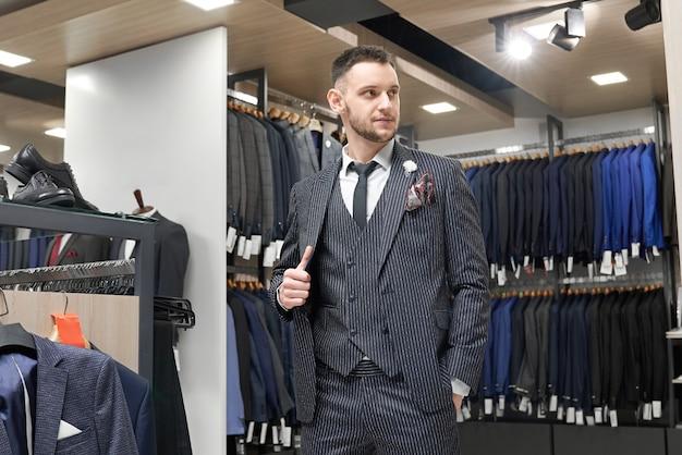 Cavalheiro posando de terno no showroom da boutique. Foto gratuita