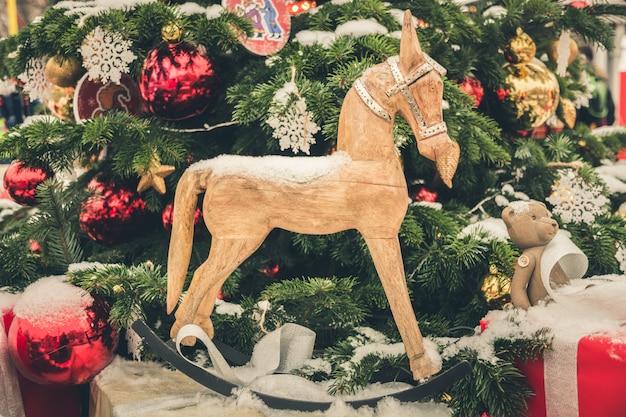 Cavalo de brinquedos de natal e neve na árvore de natal do ramo Foto Premium