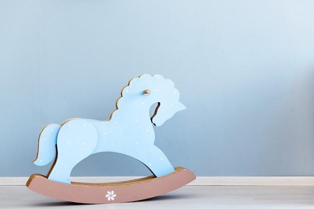 Cavalo de papelão azul, brinquedo de crianças balançando, parede azul interior Foto Premium