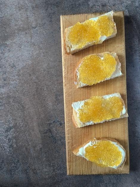 Caviar de pike em sanduíches, partes brancas de pão e manteiga em uma placa de madeira. Foto Premium