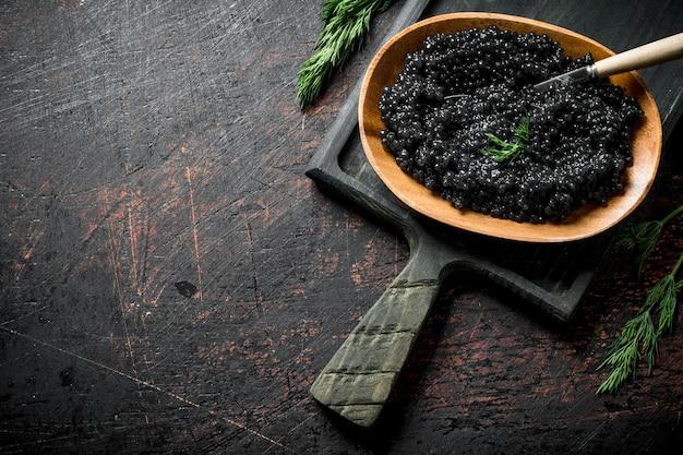 Caviar preto em uma tigela com uma colher na tábua. em rústico escuro Foto Premium