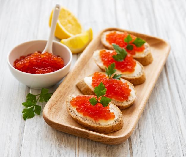 Caviar vermelho na tigela e sanduíches Foto Premium