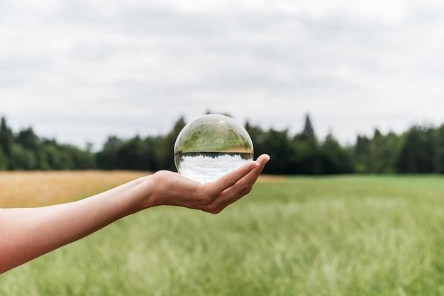 Cball na natureza com um belo prado verde e um campo de trigo dourado refletindo na esfera Foto Premium