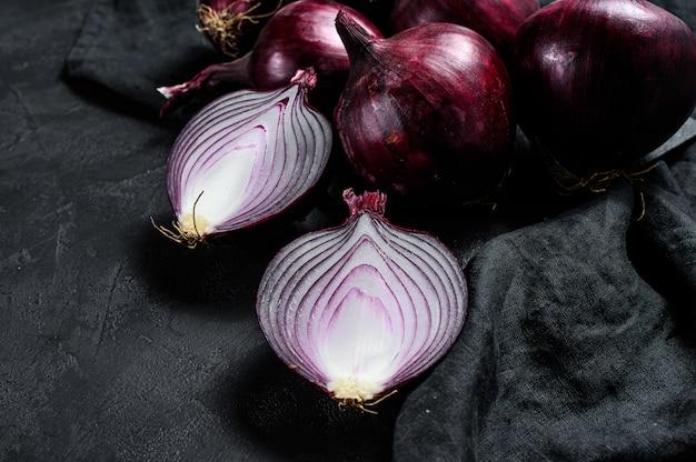 Cebola vermelha, metades de cebola. fazenda eco legumes. fundo preto. vista do topo. Foto Premium