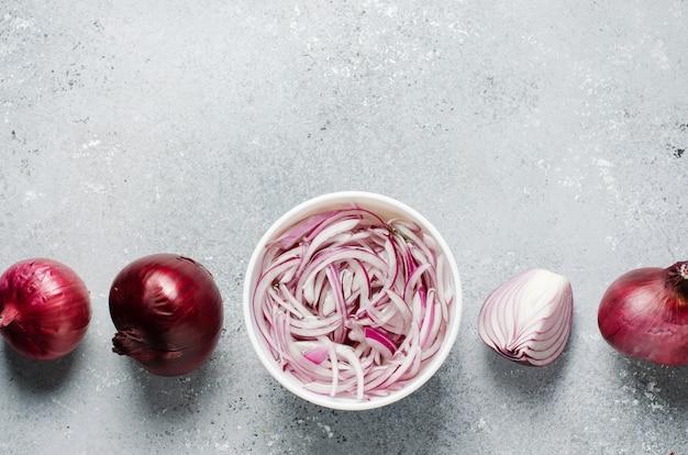 Cebola vermelha picada em conserva em vinagre em um prato branco. cebolas inteiras e fatiadas. um prato delicioso para pratos de carne e peixe. fundo cinza claro. vista superior plana Foto Premium