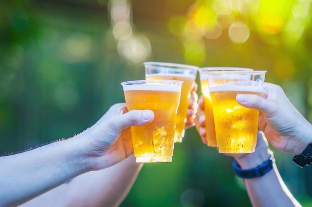 Celebração, cerveja, cheers, conceito, -, cima, mãos, segurar cima, copos cerveja, de, pessoas, grupo Foto gratuita