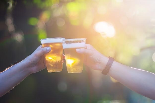 Celebração cerveja cheers conceito - close-up mãos segurando copos de cerveja Foto gratuita