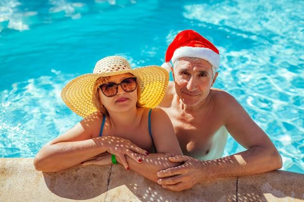 Celebração de ano novo e natal. homem de chapéu de papai noel e mulher relaxante na piscina. férias tropicais Foto Premium