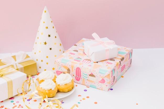 Celebração de festa de aniversário com bolinho; caixas de presente e chapéu de festa na mesa branca Foto gratuita