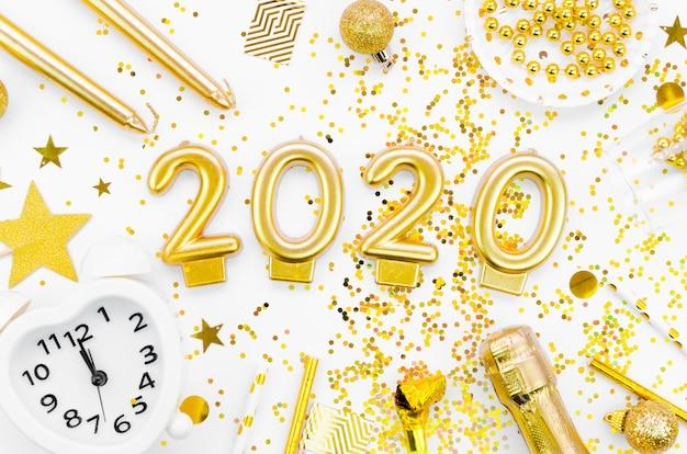 Celebração do ano novo 2020 e glitter dourado com acessórios Foto gratuita