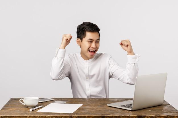 Celebração, sucesso e conceito de finanças. alegre jovem asiática regozijando-se, levantando os punhos cerrados em hooray, sim gesto, sentado a mesa, olhando a tela do laptop Foto Premium