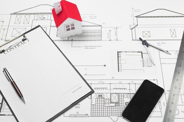 Celular e prancheta com modelo de casa pequena na planta Foto gratuita