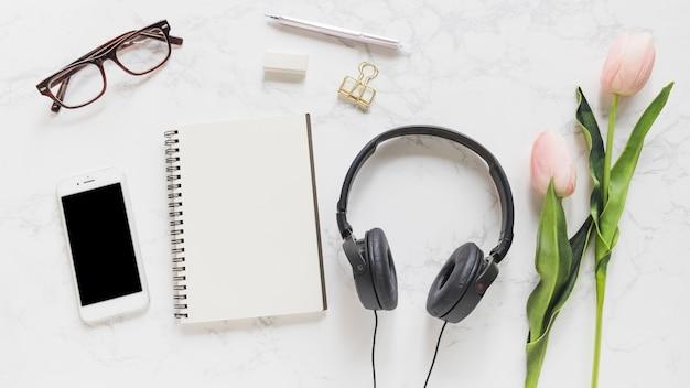 Celular; óculos; caderno; papelaria; fone de ouvido e tulipas cor de rosa no pano de fundo de mármore Foto gratuita