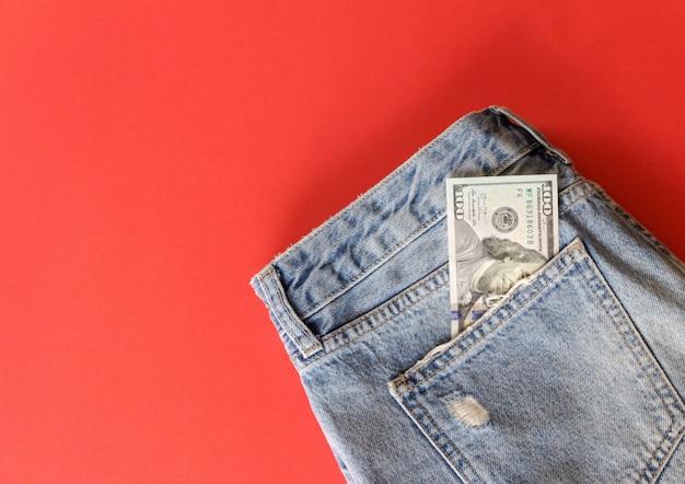 Cem dólares no bolso de calça jeans no vermelho Foto Premium