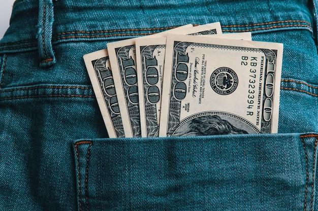 Cem notas americanas em dinheiro no bolso de trás da calça jeans. Foto Premium
