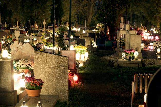 Cemitério à noite, queimando velas, lápides iluminadas à luz de velas Foto Premium