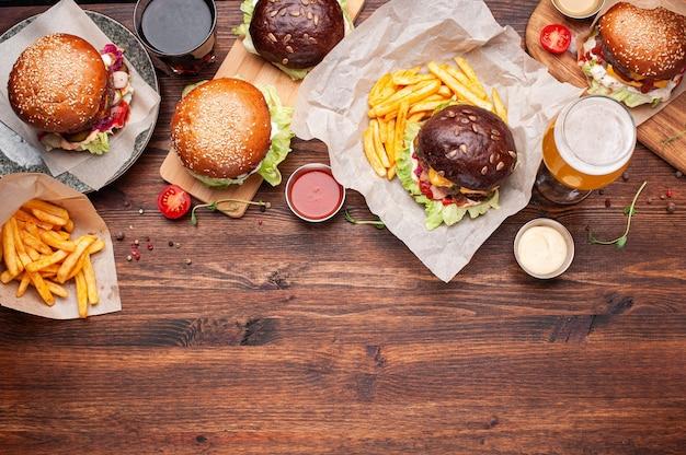 Cena da mesa de hambúrgueres, batatas fritas, drinks, molhos e vegetais. tiro horizontal com espaço para texto. Foto Premium