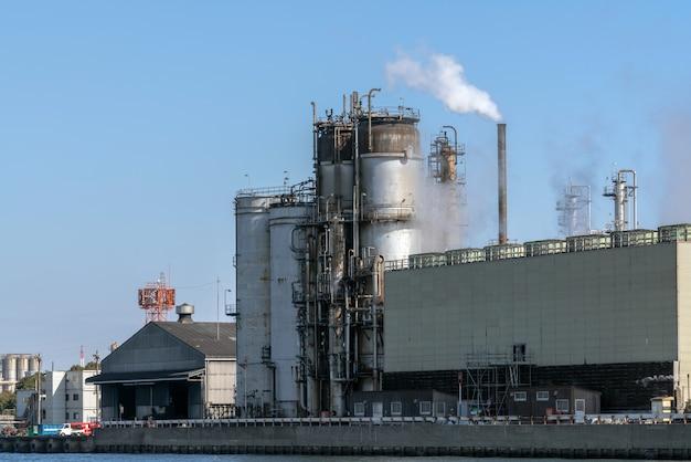 Cena da zona industial da refinaria de petróleo ao lado do rio na hora de funcionamento que têm o fumo de vapor Foto Premium