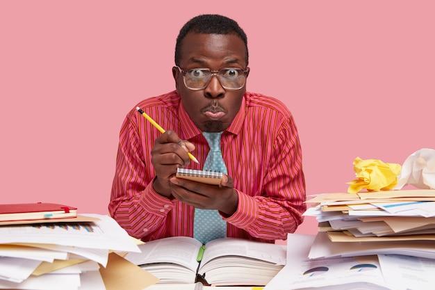 Cena horizontal de um homem negro emotivo anota informações no caderno, senta-se sozinho na mesa, faz careta, usa camisa rosa e gravata, trabalha em reportagem Foto gratuita
